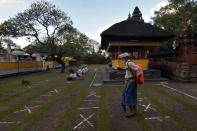 A staff member sprays an eco enzyme liquid while sanitizing a temple during the emergency restrictions imposition by the government as the number of coronavirus disease (COVID-19) cases rises, in Denpasar, Bali