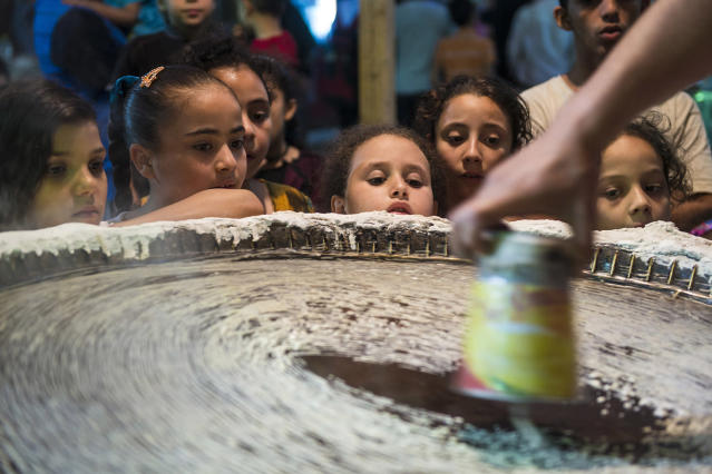 <p>Children gather around a man making Kunafa, a Middle Eastern dessert usually eaten during Ramadan, on a street at al-Baragel, Cairo, Egypt, May 25, 2017. (Photo: Mohamed Hossam/EPA) </p>
