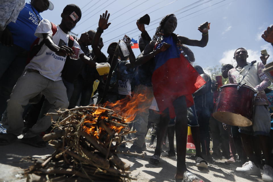 Supporters of former Haitian President Jean-Bertrand Aristide dance and drum as they wait near the airport for his expected arrival from Cuba, where he underwent medical treatment, in Port-au-Prince, Haiti, Friday, July 16, 2021. Aristide's return adds a potentially volatile element to an already tense situation in a country facing a power vacuum following the July 7 assassination of President Jovenel Moïse. (AP Photo/Fernando Llano)