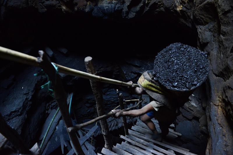 A miner slowly carries a heavy load of wet coal on a basket hundreds of feet up on wooden slats that brace the sides of a deep coal mine shaft near Rimbay village in the Indian northeastern state of Meghalaya on January 31, 2013 (AFP Photo/Roberto Schmidt)