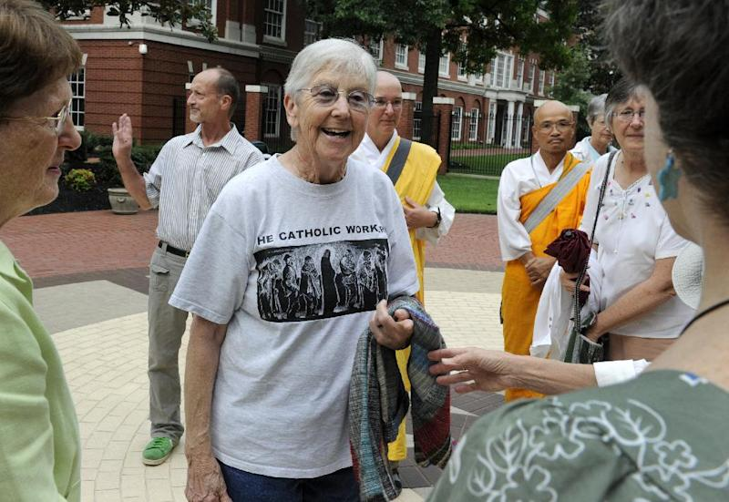 Y-12 protesters Sister Megan Rice, center, and Michael Walli, in the background waving, are greeted by supporters as they arrive for a federal court appearance Thursday, Aug. 9, 2012 in Knoxville, Tenn. Along with a third defendant third, Greg Boertje-Obed, the pair were indicted on charges stemming from their alleged July 2 infiltration of the Y-12 nuclear weapons plant in Oak Ridge, Tenn.   (AP Photo/Knoxville News Sentinel, Michael Patrick)