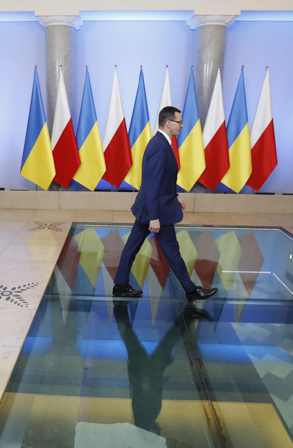 Poland's Prime Minister Mateusz Morawiecki walks to welcome Ukraine's President Volodymyr Zelenskiy as they meet in Warsaw, Poland, Saturday, Aug. 31, 2019. Zelenskiy is in Warsaw with members of his new Cabinet and will attend ceremonies marking 80 years of the start of World War II on Sunday. (AP Photo/Petr David Josek)