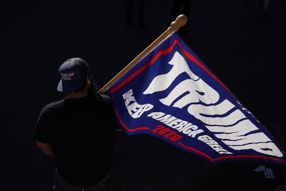 A supporter of President Donald Trump carries a Trump flag before a news conference by the Trump campaign in front of the Clark County Election Department, Thursday, Nov. 5, 2020, in Las Vegas. (AP Photo/John Locher)