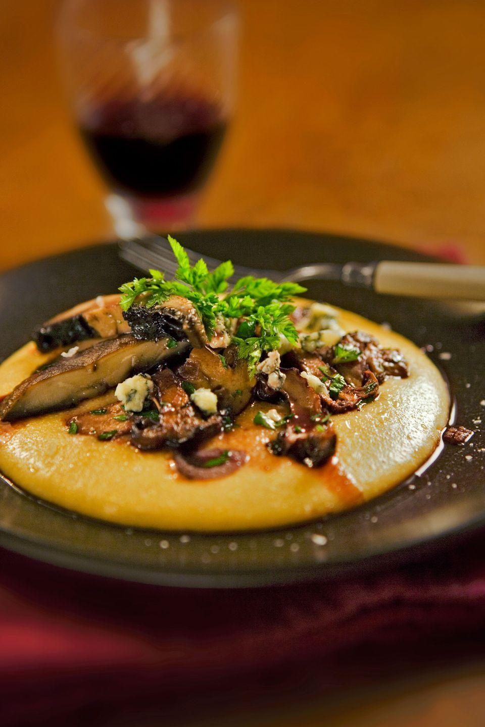 "A variation on our basic Polenta recipe, this dish pairs Madeira wine-enhanced wild mushrooms with a blue cheese- and Parmesan-spiked polenta. <a href=""https://www.countryliving.com/food-drinks/recipes/a2375/creamy-polenta-mushrooms-recipe/"" rel=""nofollow noopener"" target=""_blank"" data-ylk=""slk:Get the recipe."" class=""link rapid-noclick-resp""><strong>Get the recipe.</strong></a>"
