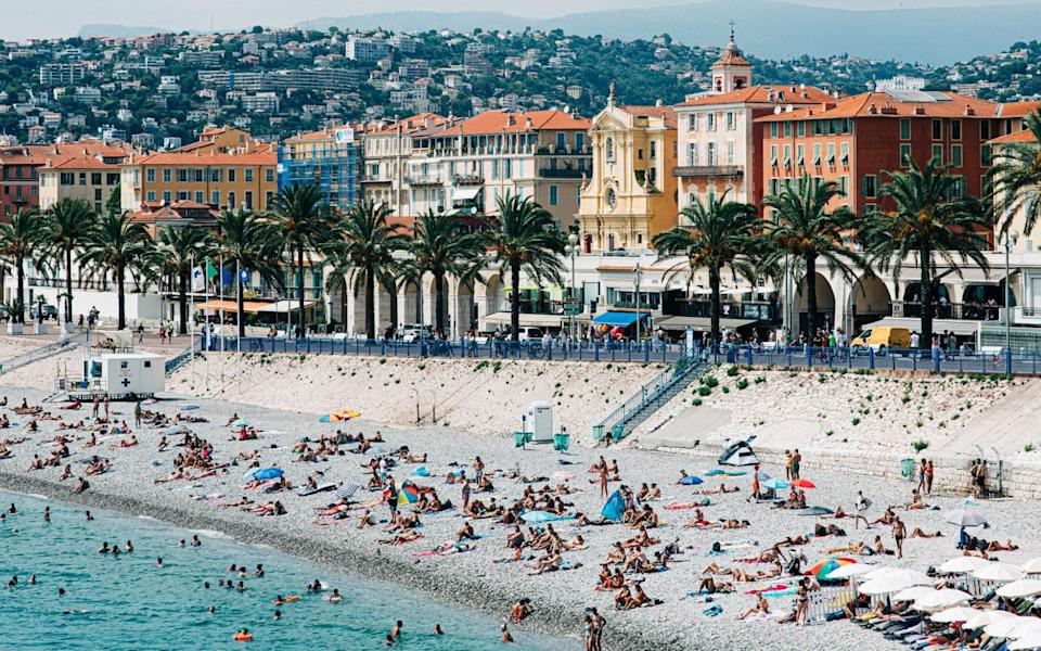 Nice beach with sunbathers and colourful buildings - Karl Hendon /Moment RF