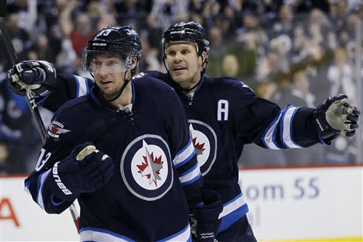 Winnipeg Jets forwards Kyle Wellwood, left, and Olli Jokinen celebrate Wellwood's goal against the Philadelphia Flyers during the second period of an NHL hockey game in Winnipeg on Saturday, April 6, 2013. (AP Photo/The Canadian Press, John Woods)