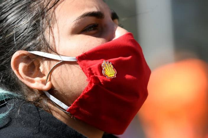 Protester wears a protective face mask during a demonstration outside of the Shell headquarters, in The Hague