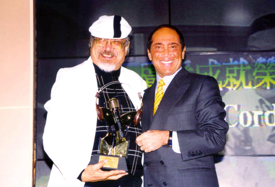 """In this undated photo released by Radio Television Hong Kong, Hong Kong DJ, Ray Cordeiro, also known as Uncle Ray, left, receives """"The Life-Time Achievement in Broadcasting Award"""" from Canadian-American singer Paul Anka in Hong Kong. After more than seven decades in radio, the 96-year-old Hong Kong DJ bid farewell to his listeners Saturday, May 15, 2021 with """"Time to Say Goodbye,"""" sung by Sarah Brightman and Andrea Bocelli. (Radio Television Hong Kong via AP)"""