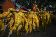 Nepalese devotees wearing protective gear as a precautionary measure against the coronavirus carry the chariot during Pachali Bhairav festival in Kathmandu, Nepal, Wednesday, Oct. 21, 2020. The festival which is usually celebrated in the night time during Dashain festival was celebrated during the day because of the pandemic. (AP Photo/Niranjan Shrestha)