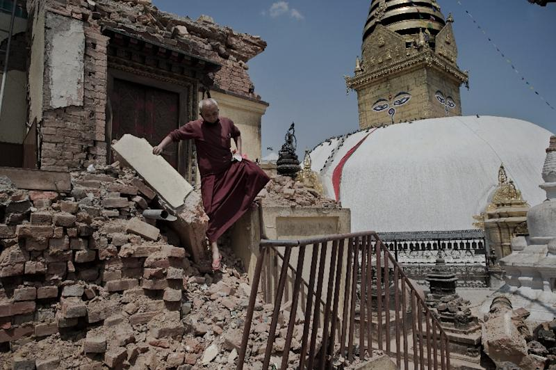 A Buddhist monk walks over the rubble of buildings near the Swayambhunath temple in Kathmandu, May 2, 2015 (AFP Photo/Nicolas Asfouri)