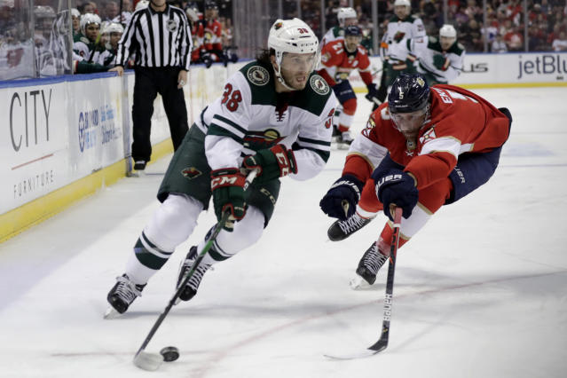 Minnesota Wild right wing Ryan Hartman (38) skates with the puck as Florida Panthers defenseman Aaron Ekblad defends during the second period of an NHL hockey game, Tuesday, Dec. 3, 2019, in Sunrise, Fla. (AP Photo/Lynne Sladky)