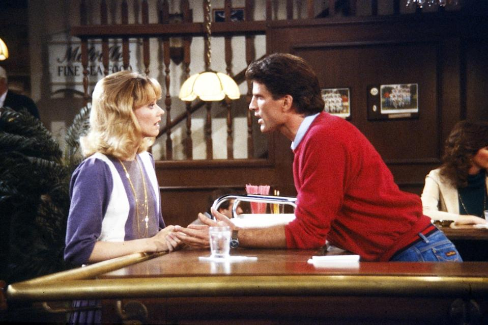 Shelley Long and Ted Danson lean on a bar looking at each other