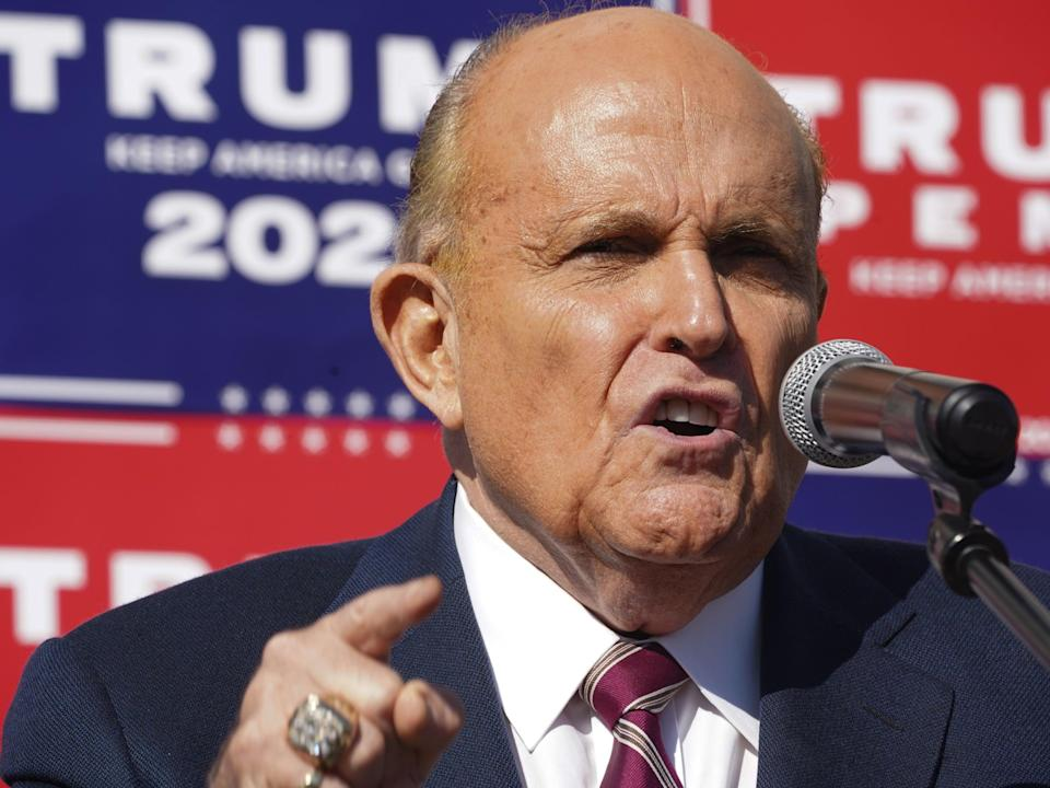 Attorney for the President, Rudy Giuliani, speaks at a news conference in the parking lot of a landscaping company on 7 November, 2020 in Philadelphia (AFP via Getty Images)