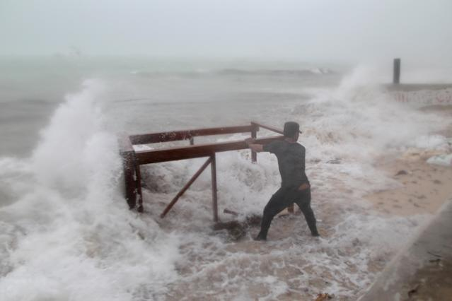 <p>A man tries to salvage a table belonging to his restaurant before the arrival of Hurricane Maria in Punta Cana, Dominican Republic, Sept. 20, 2017. (Photo: Ricardo Rojas/Reuters) </p>