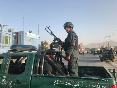 An Afghan policeman stands at the site of a blast in Kabul, Afghanistan