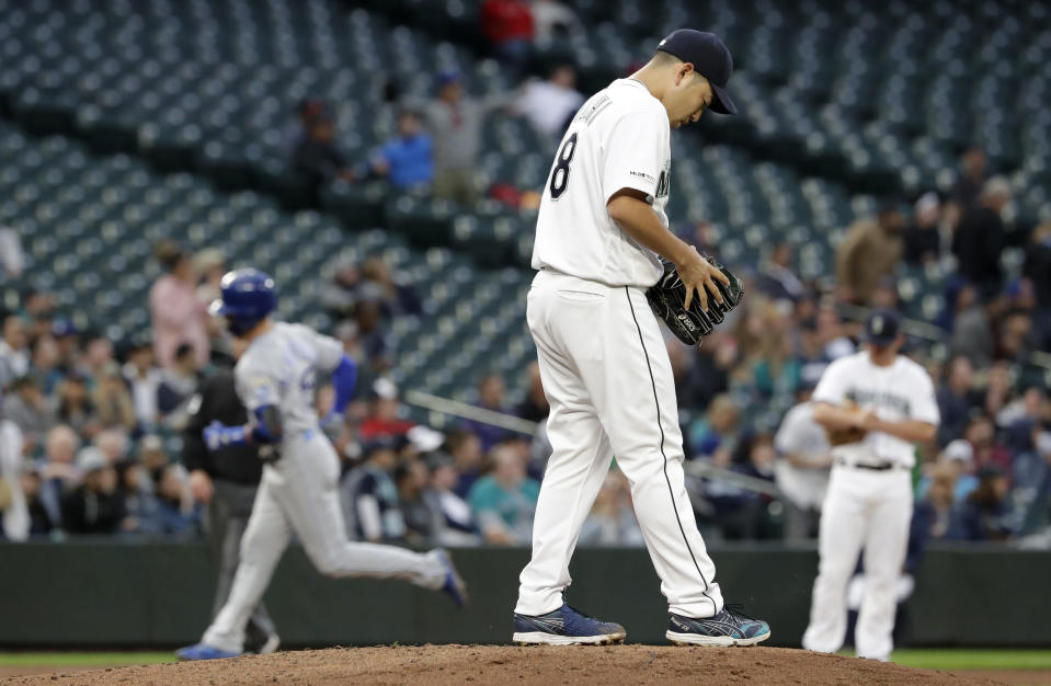 Seattle Mariners starting pitcher Yusei Kikuchi, right, looks down as Kansas City Royals' Whit Merrifield runs the bases on his three-run home run in the fourth inning of a baseball game Tuesday, June 18, 2019, in Seattle. (AP Photo/Elaine Thompson)