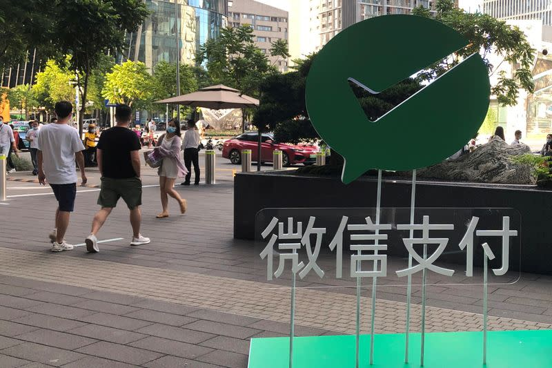 FILE PHOTO: FILE PHOTO: People walk past a Wechat Pay sign at the Tencent company headquarters in Shenzhen