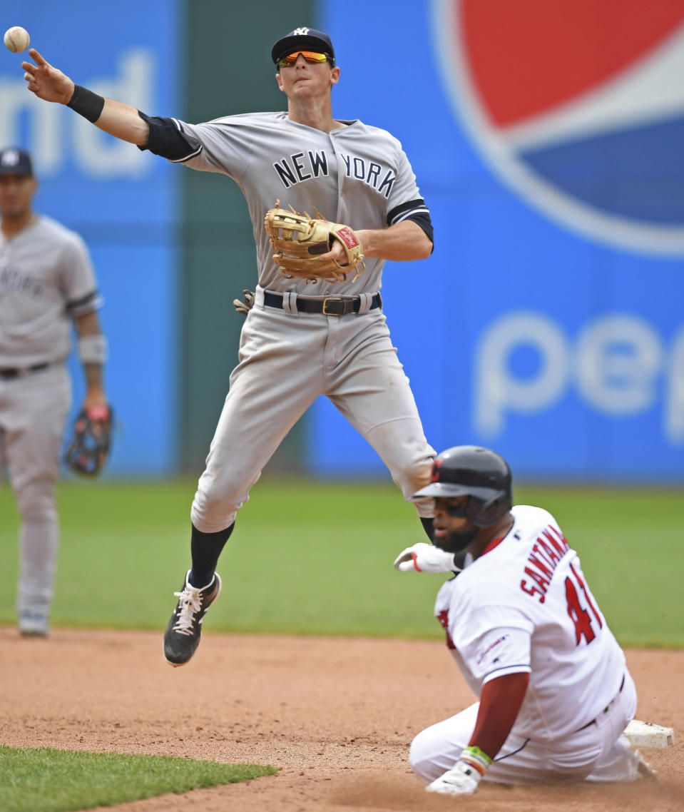 New York Yankees' DJ LeMahieu throws to first base after forcing out Cleveland Indians' Carlos Santana at Second base in the eighth inning of a baseball game, Sunday, June 9, 2019, in Cleveland. Mike Freeman would be safe at first base. The Yankees won 7-6. (AP Photo/David Dermer)