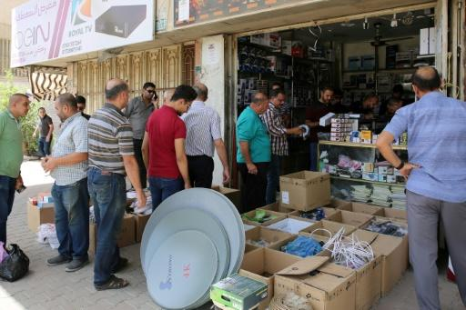 Iraqi men queue to buy satellite TV subscriptions in Baghdad on June 18, 2018, but most citizens cannot afford home pay TV packages