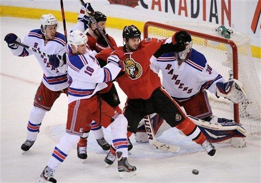 Ottawa Senators' Zenon Konopka, second from right, fights for the puck with New York Rangers' Jesse Winchester, front left, in front of Rangers goaltender Henrik Lundqvist as Rangers' Michael Del Zotto, left, and Senators' Chris Neil, rear, battle for position during the first period of Game 4 of a first-round NHL hockey Stanley Cup playoff series against the Ottawa Senators in Ottawa, Ontario, Wednesday, April 18, 2012. (AP Photo/The Canadian Press, Sean Kilpatrick)