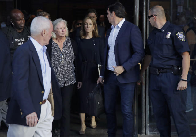 Actress Felicity Huffman, center, leaves federal court after her sentencing in a nationwide college admissions bribery scandal, Friday, Sept. 13, 2019, in Boston. (AP Photo/Elise Amendola)