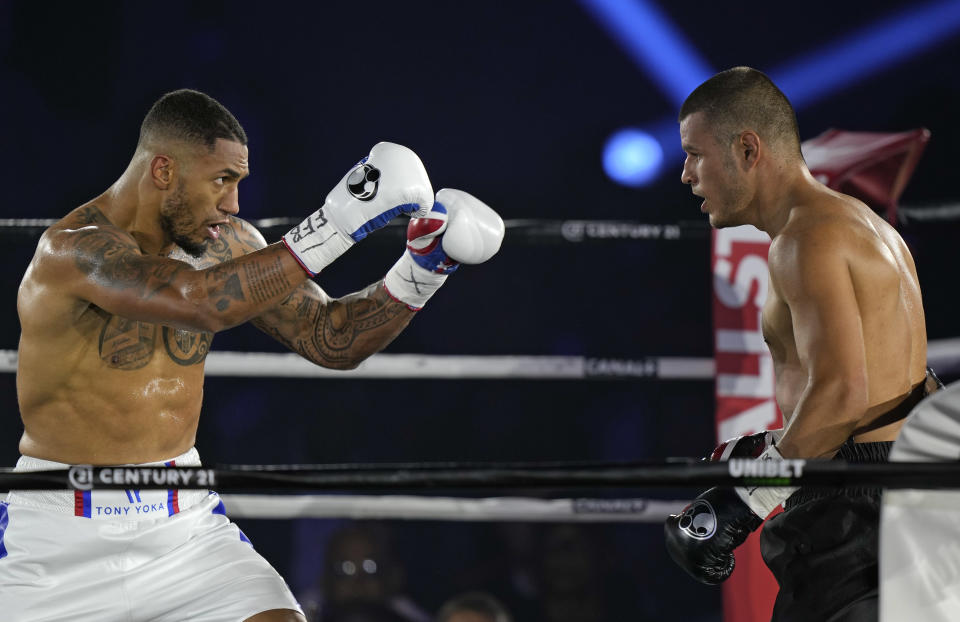 Tony Yoka of France, left, faces Croatia's Petar Milas during their heavyweight boxing fight on the central court Philippe Chatrier at the Roland Garros tennis stadium, in Paris, Friday, Sept. 10, 2021. (AP Photo/Francois Mori)