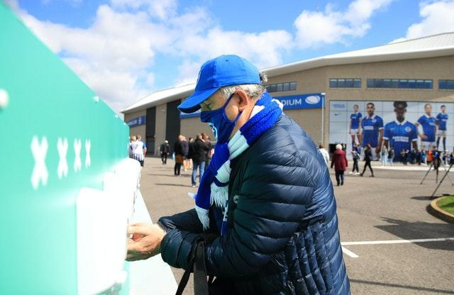 A Brighton fan uses hand sanitiser at a pilot event for the return of spectators