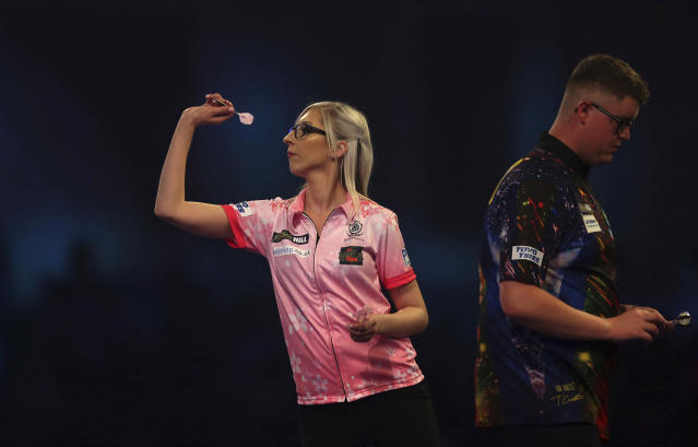 Fallon Sherrock and Ted Evetts in action at the PDC Darts World Championship at Alexandra Palace, London, Tuesday Dec. 17, 2019. Sherrock become the first female player to beat a man at the PDC World Championship after she recovered from losing the opening set to beat Ted Evetts 3-2 in front of a raucous crowd at Alexandra Palace. (Steven Paston/PA via AP)