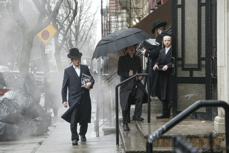 Men arrive at an Orthodox synagogue in New York's Brooklyn borough on December 30, 2019