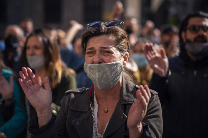 A woman cries during a protest organised by restaurant and bar owners in Barcelona, Spain, Wednesday Oct. 14, 2020. Authorities in northeastern Spain ordered shut all bars and restaurants for two weeks. Restaurant and bar owners protested the measure in Catalonia, saying that they already suffered a huge hit when closed in the nationwide lockdown in the spring. (AP Photo/Emilio Morenatti)