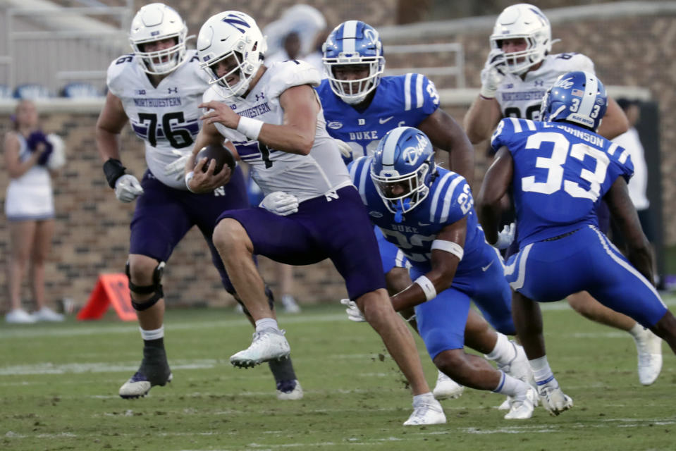 Northwestern quarterback Andrew Marty (7) evades Duke safety Lummie Young IV (23) on a run during the second half of an NCAA college football game in Durham, N.C., Saturday, Sept. 18, 2021. (AP Photo/Chris Seward)