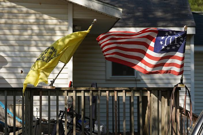 """A Three Percenter flag and a Gadsden Flag fly onthe home of Michael Null in Plainwell, Mich., on October 9, 2020. Null one of 13 suspects accused of plotting to abduct and possibly harm Michigan Gov. Gretchen Whitmer.<span class=""""copyright"""">Ryan Garza—USA Today Network/Sipa USA</span>"""