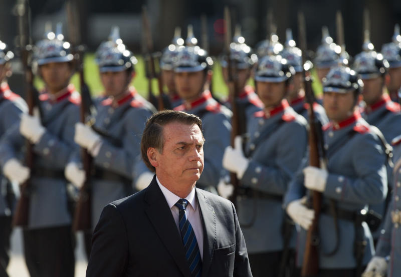 "Brazil's President Jair Bolsonaro walks past the ""Granaderos"" presidential guard during a welcoming ceremony at La Moneda, in Santiago, Chile, Saturday, March 23, 2019. Bolsonaro is on the second day of his two-day visit. (AP Photo/Esteban Felix)"