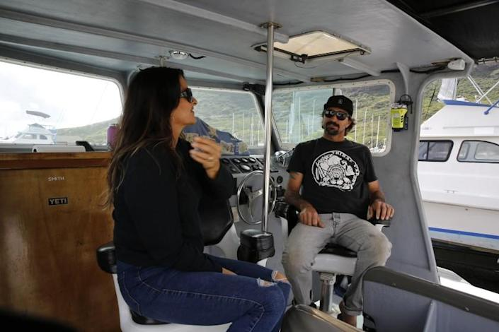 Cynthia and Lance Keener, owners of Ohana Fishing Charters, sit on their boat in Lihue, Hawaii, Thursday, March 4, 2021. The rural island in Hawaii is one of the world's most sought-after vacation destinations, but it has been nearly impossible to visit for most of the past year because of quarantine and other coronavirus restrictions. Keener said he lost nearly all of his business when the county shut down last March. Things haven't gotten any better, and he looks forward to when the state lifts restrictions in April. (AP Photo/Caleb Jones)
