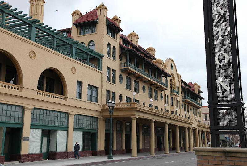 """A man walks past the historic Hotel Stockton Wednesday, Feb. 29, 2012, in Stockton, Calif. A red, white and blue sign declaring Stockton an """"All-America City"""" still adorns City Hall, but the building's crumbling facade tells the real story of the community's recent fortunes. Since the sign went up nearly a decade ago, Stockton has twice topped Forbes magazine's list of """"America's most miserable cities."""" And now another unflattering title could be headed its way: largest American city to declare bankruptcy. (AP Photo/Ben Margot)"""