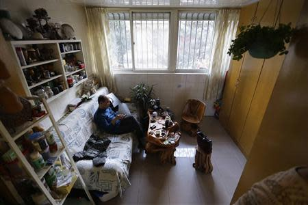 51 year-old Tian Lianpu, father of the late Tian Yao, looks at his mobile phone as he drinks tea at home in Beijing