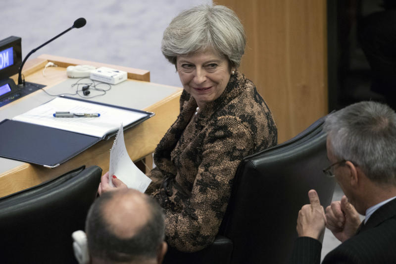 British Prime Minister Theresa May speaks to an aid during a high level meeting on the situation in Libya, Wednesday, Sept. 20, 2017 at United Nations headquarters. (AP Photo/Mary Altaffer)