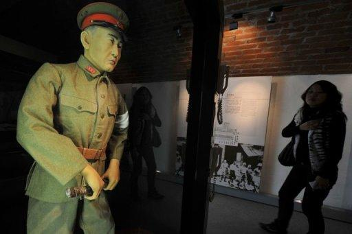 A woman reacts when she sees a scale model of a Japanese Kempeitai (military police) at a Museum in Hong Kong