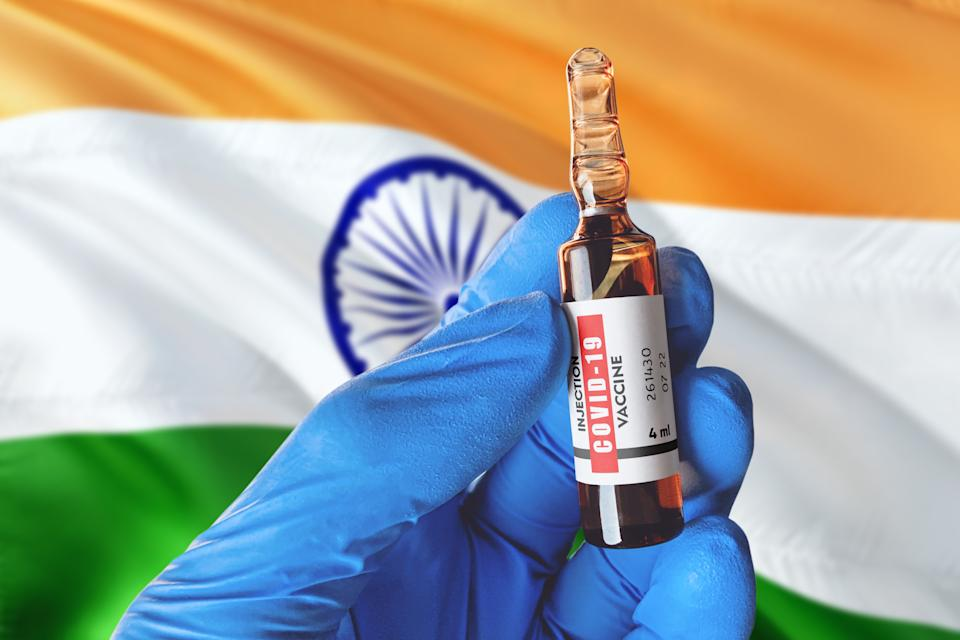 India flag with Coronavirus Covid-19 concept. Doctor with blue protection medical gloves holds a vaccine bottle. coronavirus covid 19 vaccine research.