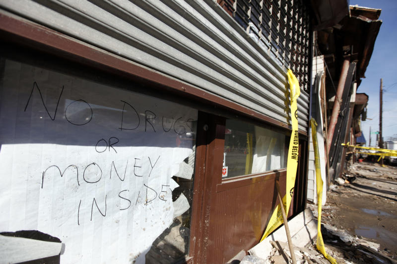 A sign proclaiming a lack of valuables inside is posted in the door of a veterinary clinic on a storm- and fire-ravaged block in Rockaway Beach, Tuesday, Nov. 6, 2012, in the the Queens borough of New York. Weather experts have some good news for beleaguered coastal residents in the Northeast: A new storm that threatened to complicate Hurricane Sandy cleanup efforts now looks like it will be weaker than expected. (AP Photo/Jason DeCrow)