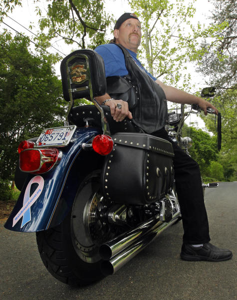 """In this May 3, 2012 photo, breast cancer survivor Robert Kaitz sits on his motorcycle, which displays a male breast cancer survivor ribbon, in Severna Park, Md. Kaitz thought a small growth under his left nipple was just a harmless cyst. By the time he had it checked out in 2006, almost two years later, the lump had started to hurt. The diagnosis of breast cancer was a shock. """"I had no idea in the world that men could even get breast cancer,"""" Kaitz said. Now Kaitz does frequent self-exams and has mammograms every year. The American Cancer Society estimates 1 in 1,000 men will get breast cancer, versus 1 in 8 women. (AP Photo/Patrick Semansky)"""
