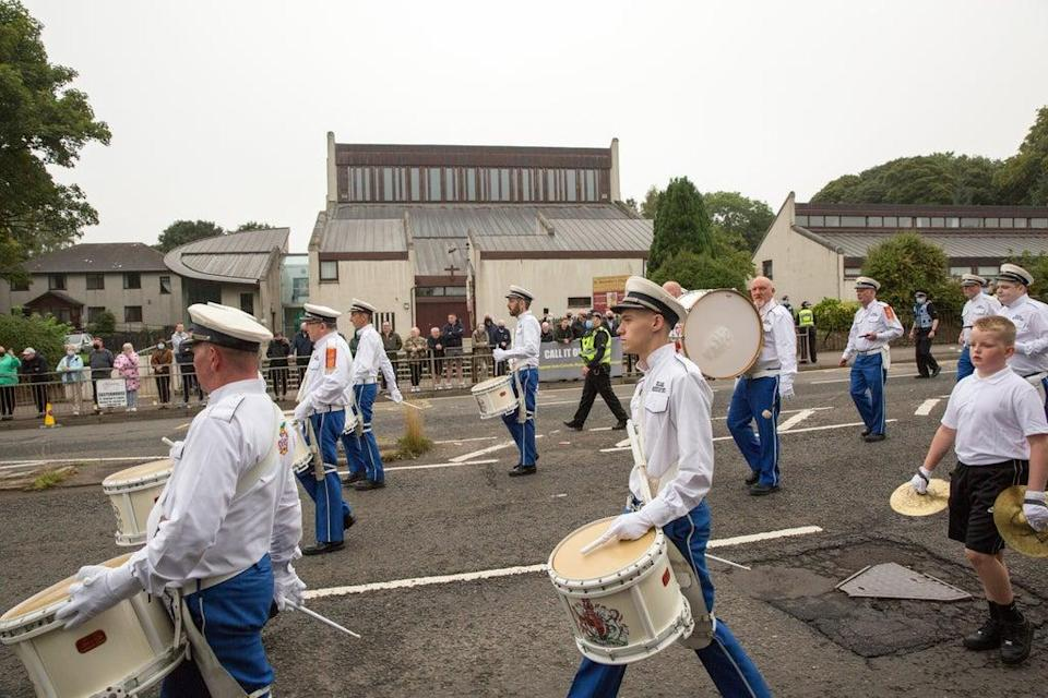 A silent Orange Order band passes by (Robert Perry/PA) (PA Wire)
