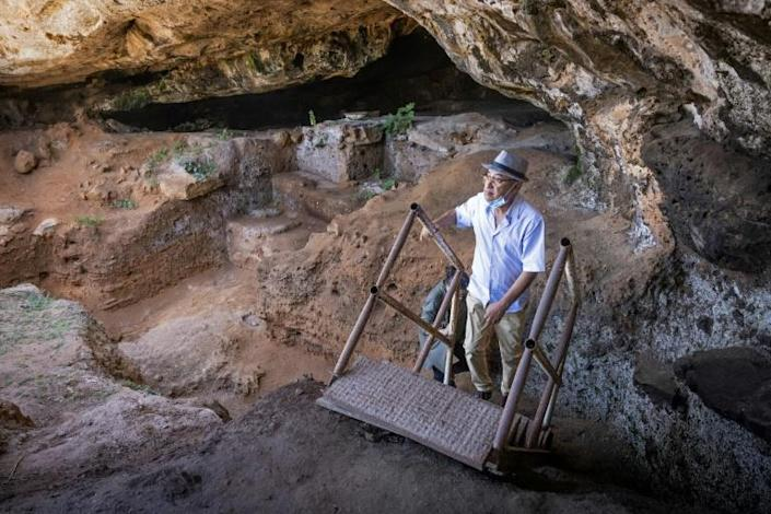 Archeologists walk to enter the cave, scene of the latest significant archaeological finding in Morocco (AFP/FADEL SENNA)