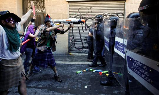 "<p>A protester squirts a water gun at Catalan regional police in full riot gear during a protest over the eviction of squatters earlier in the week from ""the Expropriated Bank,"" in Barcelona, May 29, 2016. <em>(Reuters/Albert Gea)</em> </p>"