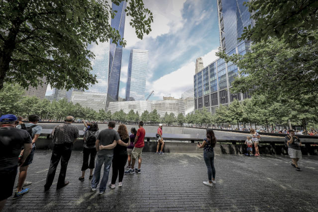 <p>Visitors gather to pay tribute to the victims of the 9/11 attacks near one of two reflecting pools at the National September 11 Memorial & Museum on Aug. 18, 2018. (Photo: Gordon Donovan/Yahoo News) </p>