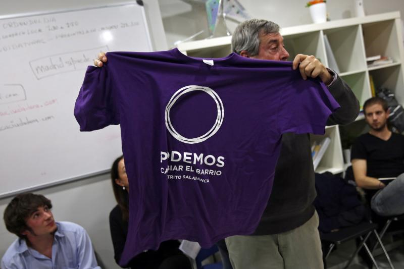 "A man shows a Podemos t-shirt for sale to participants of their local assembly at Madrid's Salamanca district December 18, 2014. In just a year since its founding, the party ""Podemos"" - We Can - has overturned the two party system in place since Spain embraced democracy in the 1970s. It is now polling around even with the ruling People's Party (PP) and main opposition Socialists, and has even led in some polls. The shirt reads, ""We can change the neighbourhood. Salamanca district"". Picture taken December 18, 2014. REUTERS/Susana Vera (SPAIN - Tags: POLITICS)"