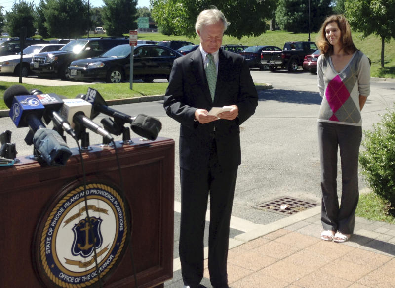 Rhode Island Gov. Lincoln Chafee reviews notes before speaking outside a department of motor vehicles office Wednesday, Sept. 4, 2013, in Cranston, R.I. Chafee said he is not running for a second term, bowing out of what was expected to be a fierce primary in his new Democratic Party. Spokeswoman Christine Hunsinger stands at right. (AP Photo/Michelle R. Smith)
