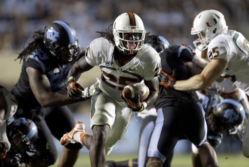 Miami's Dallas Crawford (25) carries the ball against North Carolina during the second half of an NCAA college football game in Chapel Hill, N.C., Thursday, Oct. 17, 2013. Miami won 27-23. (AP Photo/Gerry Broome)