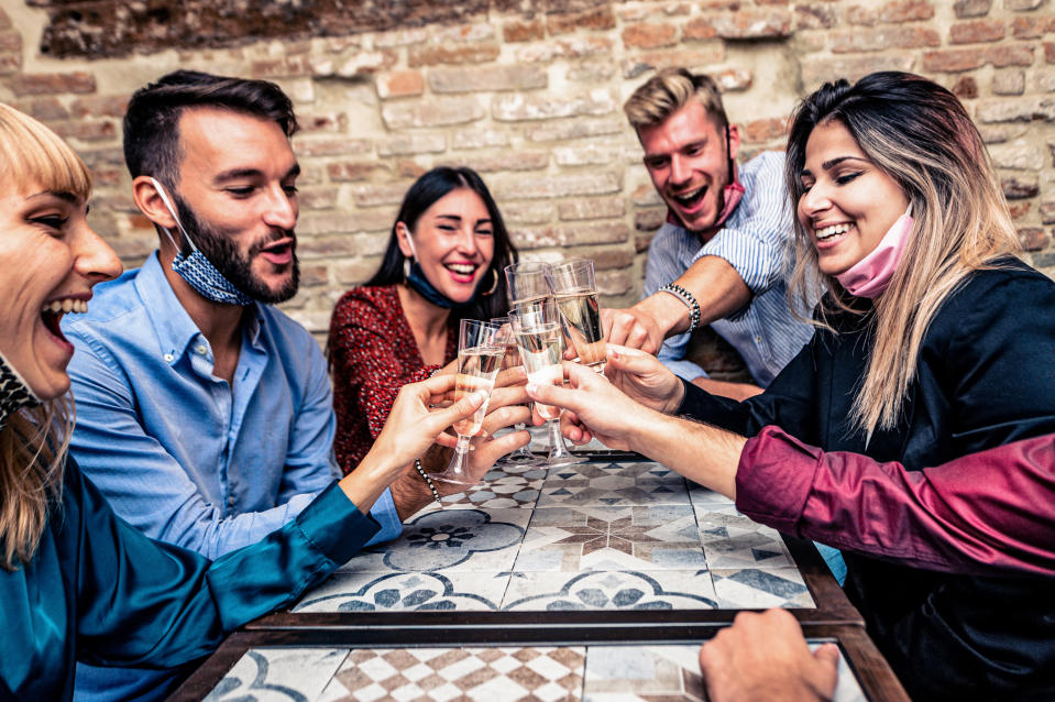 Christmas party! Young people with face mask toasting with champagne flutes in coronavirus time - Multiethnic friends congratulating each other on the new year eve - Celebration and nightlife, holiday background, selective focus