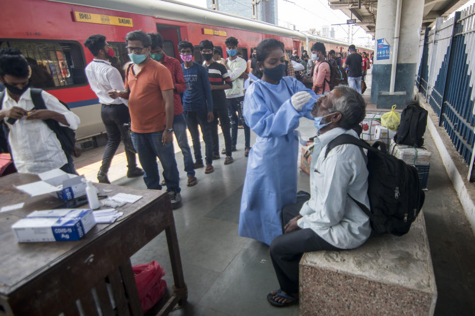 MUMBAI, INDIA - MAY 8: Healthcare worker collects swab samples of passengers arriving from outstation trains at Dadar station, on May 8, 2021 in Mumbai, India. (Photo by Pratik Chorge/Hindustan Times via Getty Images)